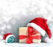 Коробка с подарком на рождество и шляпа santa на серой предпосылке Стоковые Фото