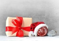 Коробка с подарком на рождество и шляпа santa на серой предпосылке Стоковые Изображения RF
