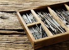 Коробка с сверлами на деревянной предпосылке Стоковая Фотография