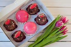 Коробка с тортами на таблице около тюльпанов Стоковые Изображения