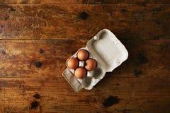 Коробка яичек на деревянном столе Стоковые Фото
