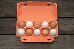 Коробка яичек ans органического коричневого цвета белых на деревянной доске Взгляд сверху Стоковые Изображения RF