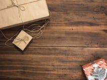 Коробки в бумаге ремесла, бумаге eco на деревянном столе Взгляд сверху Пакеты или подарки связанные с шпагатом Обернутая бумага Б Стоковые Изображения RF