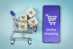 Коробки в корзине и смартфоне на голубой предпосылке Концепция: онлайн покупки, коммерция e и доставка товаров стоковые фотографии rf