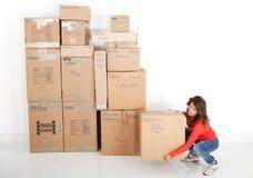 Коробки молодой женщины moving Стоковые Изображения