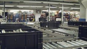 Коробки на конвейерной ленте в большом автоматизированном складе