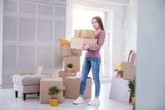 Коробки нося жизнерадостной молодой женщины с пожитками к новому дому Стоковая Фотография RF
