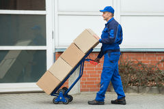 Коробки нося работника доставляющего покупки на дом на ручной тележке Стоковое Изображение