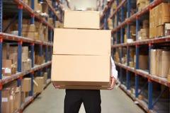 Коробки нося человека в пакгаузе стоковое фото