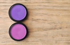 2 коробки пинка и фиолета теней для век на деревянной таблице Стоковое Изображение RF