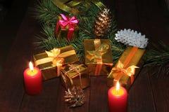 Коробки подарка рождества покрашенные, конусы, рождественская елка и свечи на деревянном столе Состав знаменитостей селективно Стоковое Фото