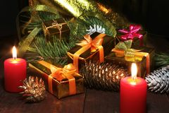 Коробки подарка рождества покрашенные, конусы, рождественская елка и свечи на деревянном столе Состав знаменитостей селективно Стоковая Фотография