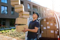 Коробки работника доставляющего покупки на дом падая стоковое фото