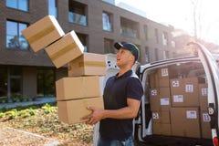 Коробки работника доставляющего покупки на дом падая стоковая фотография rf