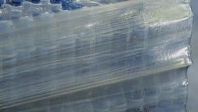Коробки с бутылками воды упакованы в ленте полиэтилена видеоматериал