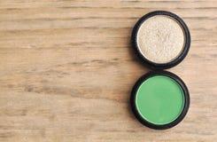 2 коробки с зеленым цветом и тени для век золота на деревянной таблице Стоковое фото RF