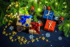 Коробки с подарками на предпосылке ветвей, конусов и гирлянд ЕЛИ Стоковая Фотография