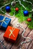 Коробки с подарками на предпосылке ветвей, конусов и гирлянд ЕЛИ Стоковые Изображения