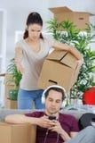 Коробки упаковки женщины moving и ленивый парень Стоковые Фото