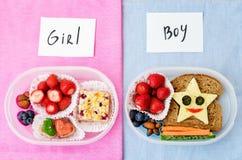 Коробки школьного обеда для девушки и мальчика с едой в форме потехи Стоковые Изображения RF