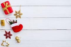 Коробки gif рождества, хлопь снега, красный носок, шарик рождества и тросточка конфеты на белой деревянной доске Стоковая Фотография RF