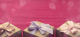 Коробки Kraft состава 3 знамени праздничные с подарками на яркой розовой предпосылке Стоковые Изображения RF