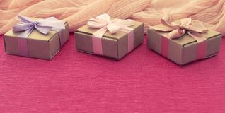 Коробки Kraft состава 3 знамени праздничные с подарками на яркой розовой предпосылке Стоковое фото RF