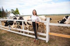 Коровы девушки счастья подавая на ферме Молодая взрослая freckled корова питания девушки на поле деревни в осени и игре с животны Стоковое Изображение RF