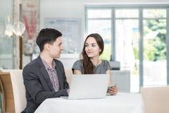 Корпоративная встреча! Молодые предприниматели сидя на таблице и Стоковые Фотографии RF