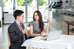 Корпоративная встреча! Молодые предприниматели сидя на таблице и Стоковое Изображение