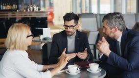 Корпоративные управляющие зреют предприниматели говоря в кафе обсуждая работу акции видеоматериалы