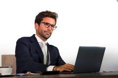 Корпоративный портрет молодого привлекательного и эффективного бизнесмена работая на столе портативного компьютера офиса уверенно стоковые изображения rf