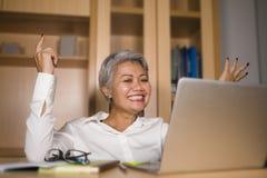 Корпоративный портрет привлекательной и счастливой успешной зрелой азиатской женщины работая на усмехаться стола ноутбука уверенн стоковые изображения