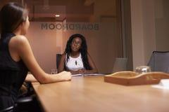 2 корпоративных коммерсантки на встрече вечера в офисе Стоковые Фото