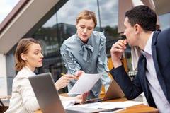 3 корпоративных люд обсуждая важные возможности компании Стоковая Фотография RF