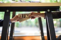 Коррумпированный бизнесмена руки герметизируя дело с рукопожатием и получая деньги взяткой Стоковое Фото