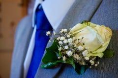 Корсаж белой розы приколотый к серому костюму стоковые фото