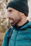 Косая съемка небритого человека с темной толстой бородой, носит теплое har и анорак, смотрит задумчиво в сторону, представляет сн стоковые фото