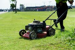 косилка человека лужайки травы вырезывания Стоковые Фото