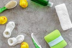 Косметика ванны установленная для детей, полотенца и игрушек на сером космосе взгляд сверху предпосылки для текста Стоковая Фотография