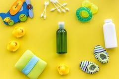 косметика ванны установленная для детей, полотенца и игрушек на желтой картине взгляд сверху предпосылки Стоковое Изображение RF