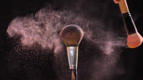 Косметика и концепция красоты Косметическая щетка с порошком пастельного пинка косметическим на черной предпосылке сток-видео