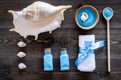 Косметика курорта установила с солью моря для ванны и раковиной на деревянном взгляд сверху предпосылки Стоковая Фотография RF