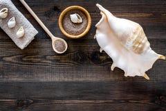 Косметика курорта установила с солью моря для ванны и раковиной на деревянном модель-макете взгляд сверху предпосылки Стоковое Фото