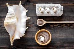 Косметика курорта установила с солью моря для ванны и раковиной на деревянном взгляд сверху предпосылки Стоковые Изображения