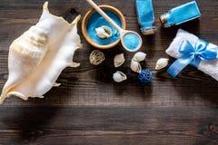 Косметика курорта установила с солью моря для ванны и раковиной на деревянном модель-макете взгляд сверху предпосылки Стоковые Фото