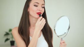 Косметика прикладывать косметическую женщину красного цвета губной помады сток-видео