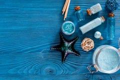 Косметики мертвого моря Соль моря, голубая глина и лосьон на голубом copyspace взгляд сверху предпосылки деревянного стола Стоковая Фотография