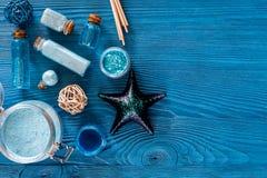 Косметики мертвого моря Соль моря, голубая глина и лосьон на голубом copyspace взгляд сверху предпосылки деревянного стола Стоковая Фотография RF