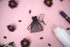 Косметики на таблице на женщине Косметические сумка, косметика и продукты гигиены Розовая предпосылка для текста стоковые фотографии rf